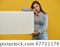 Beautiful girl holding white mock up placard 67721176