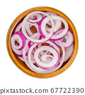 Red onion rings in wooden bowl. Slices of the onion cultivar Allium cepa with purplish red skin and white flesh tinged with red. Closeup, from above, on white background, isolated, macro food photo. 67722390
