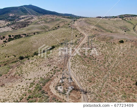 Aerial view of electricity transmission pylon in dry valley landscape 67723409