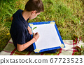 Painter teenager draws leaves in nature 67723523