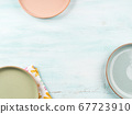 Pastel color dishes on turquoise background 67723910