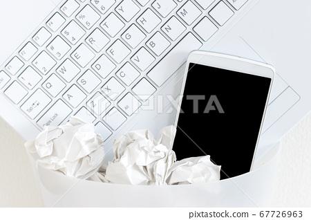 筆記本電腦和智能手機丟在垃圾桶裡。數字排毒的形象 67726963