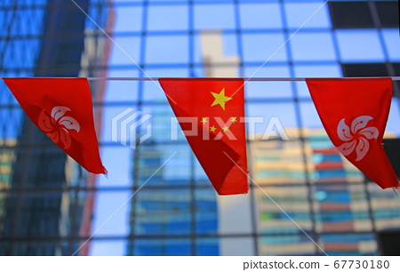 chinese and hong kong flags blow in the wind with glass building background 67730180