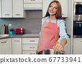 Nice young woman cooking something by the stove in her kitchen 67733941
