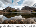 Rocky mountains with cloudy in blue sky reflection 67735436