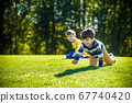 Two happy boys playing on fresh green grass 67740420