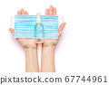 Female hands holding liquid soap or hand sanitizer spray dispenser and medical protective mask isolated on white background with clipping path 67744961