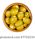 Green olives stuffed with garlic cloves in wooden bowl. Big olives, fruits of Olea europaea, hand filled with pickled garlic pieces. Closeup from above, on white background, isolated macro food photo. 67750234