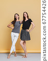 Two happy sisters in casual clothes posing on yellow background 67754426