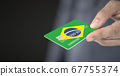 Man gives plastic bank card with printed flag of Brazil. Fictional numbers 67755374