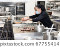 Chef in uniform cooking in a commercial kitchen. Female cook wearing apron standing by kitchen 67755414
