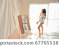 full length asian woman artist in white shirt drinking coffee while drawing picture 67765538