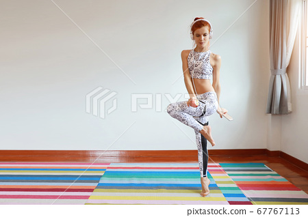 young attractive caucasian woman in sportswear listening and dancing music from mobile and headphone 67767113
