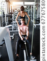 full length sporty caucasian fitness man using exercise machine in gym with caucasian trainer woman 67767580