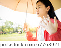 Child girl is holding umbrella uv protection from sunlight ray,high temperature on sunny day,prevent heatstroke,face skin from bright sun,sunburn very hot,using umbrella to cover the strong sun light 67768921