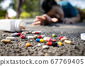 Sick asian man have any chronic health conditions,heart attack lying on the floor after falling down,male people trying to reach for a bottle of medicine,lot of pills at the street,medical emergency 67769405