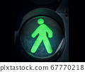 traffic light with green man on a black background  67770218