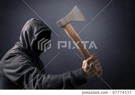 Hooded man with an axe in the dark 67774537