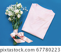 Mockup of a folded t-shirt placed near white 67780223