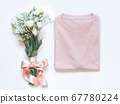 Mockup of a folded t-shirt placed near white 67780224