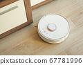 Smart House. Vacuum cleaner robot runs on wood floor in a living room 67781996