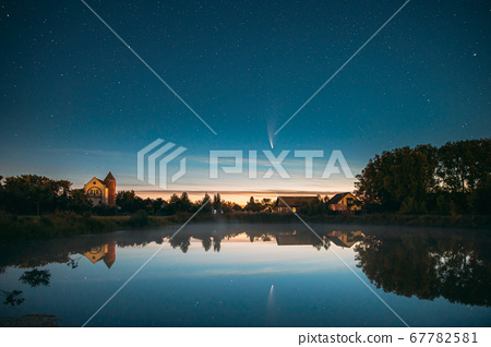 Dobrush, Belarus. Comet Neowise C2020f3 In Night Starry Sky Reflected In Small Lake Waters. 67782581
