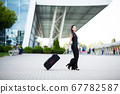 Vacation. Smiling female passenger proceeding to exit gate pulling suitcase through airport concourse. 67782587