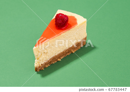 Cheesecake slice with raspberry sauce topping. 67783447