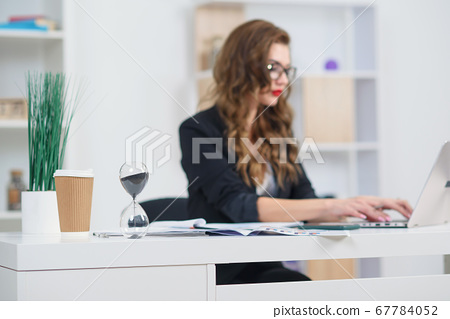 Close up photo of hourglass standing at desk and beautiful business woman working at office.. 67784052