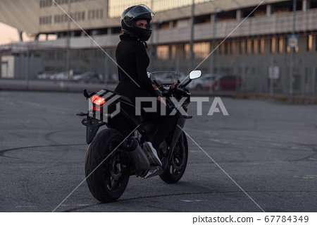 Adorable girl in black tight body suit and full-face helmet rides on stylish motorcycle at urban outdoors parking in evening. Freedom and active lifestyle concept. Totally black. 67784349