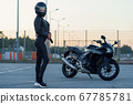 Sexy biker woman in black leather jacket and full face helmet stands near stylish sports motorcycle. Urban parking, sunset in big city. Traveling and active hipster lifestyle. 67785781