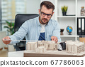 Handsome caucasian senior architect at glasses working on a construction project and examines the model on which he works. 67786063