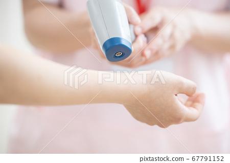 用非接觸式溫度計測量溫度的醫療護士(手) 67791152