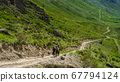 Mountain guide on horseback with dogs on the road 67794124
