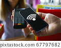 Man do contactless payment for product by phone. 67797682