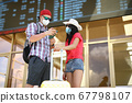 Woman in hat stand with man on train station and study schedule in phone and scoreboard with yellow suitcase. 67798107