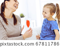 Mother's day concept. Child daughter congratulates mom and gives her postcard with red heart shape. Mum and girl happy smiling and hugging. Family fun and holiday 67811786