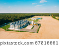 Aerial View Modern Granary, Grain-drying Complex, Commercial Grain Or Seed Silos In Sunny Spring Rural Landscape. Corn Dryer Silos, Inland Grain Terminal, Grain Elevators Standing In A Field 67816661