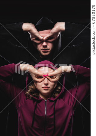 A low key pair of imaginary super heroes man and woman make gestures mask with hands. The hackers are among us. Couple in hoods makes stern faces 67820179