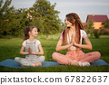 Young mother with dreadlocks and little daughter are doing yoga exercises in lotus position on grass in the park at the day time. Concept of friendly family and of summer vacation. 67822637