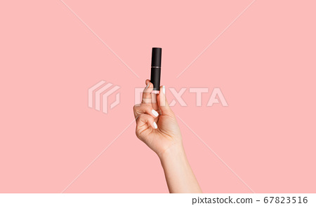 Beauty and makeup. Young lady holding tube of lipstick over pink background, closeup 67823516