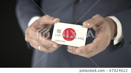 Businessman holds plastic bank card with printed flag of Japan, fictional numbers 67824622