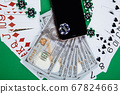 Smartphone and poker chips with playing cards and money banknotes on a green table. Online casino concept 67824663