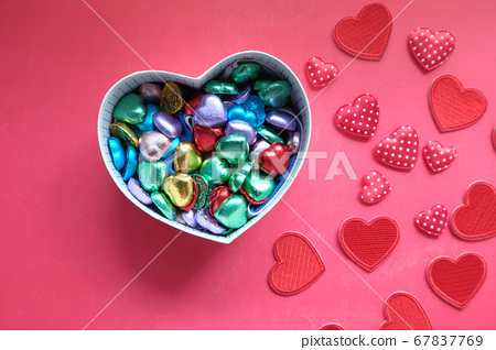 heart shape gift box with candy on red background  67837769