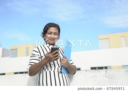 Indian corporate woman holding and reading her 67840951