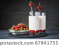 Strawberry milk smoothie in glass with straw on a 67841755