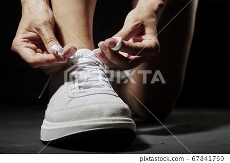 Woman hands tying shoelaces on sneakers on dark 67841760