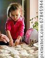 Grandmother and granddaughter sculpt dumplings 67845944