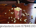 Popcorn flying out of cardboard box. red and white striped popcorn bucket with flying popcorn in the living room, movie or cinema concept 67846193