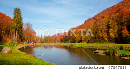 small lake in autumn park. forest on the hills in 67847011